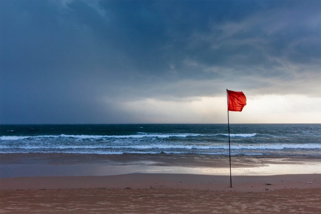 View of Beach with Storm Approaching with Warning Flags